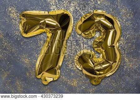 The Number Of The Balloon Made Of Golden Foil, The Number Seventy-three On A Gray Background With Se