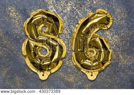The Number Of The Balloon Made Of Golden Foil, The Number Eighty-six On A Gray Background With Sequi