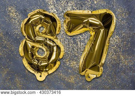 The Number Of The Balloon Made Of Golden Foil, The Number Eighty-seven On A Gray Background With Seq