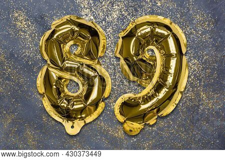 The Number Of The Balloon Made Of Golden Foil, The Number Eighty-nine On A Gray Background With Sequ