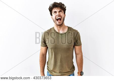 Hispanic man standing over isolated white background angry and mad screaming frustrated and furious, shouting with anger. rage and aggressive concept.