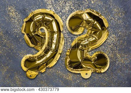 The Number Of The Balloon Made Of Golden Foil, The Number Ninety-two On A Gray Background With Sequi