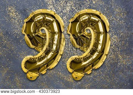 The Number Of The Balloon Made Of Golden Foil, The Number Ninety-nine On A Gray Background With Sequ