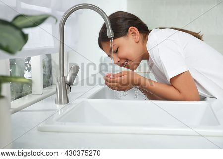 Girl Drinking Tap Water Over Sink In Kitchen