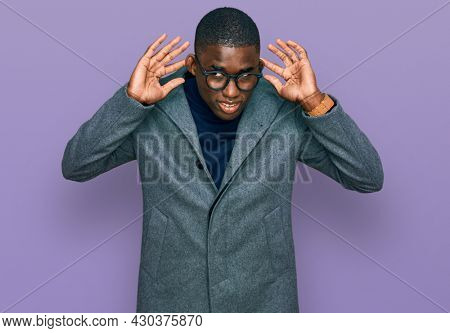 Young african american man wearing business clothes and glasses trying to hear both hands on ear gesture, curious for gossip. hearing problem, deaf