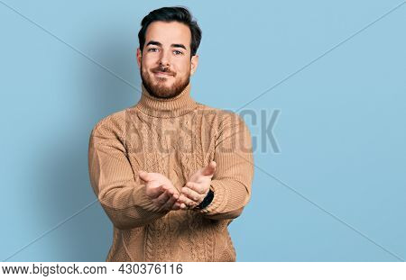 Young hispanic man wearing casual clothes smiling with hands palms together receiving or giving gesture. hold and protection