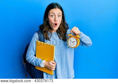 Young brunette student woman holding alarm clock afraid and shocked with surprise and amazed expression, fear and excited face.