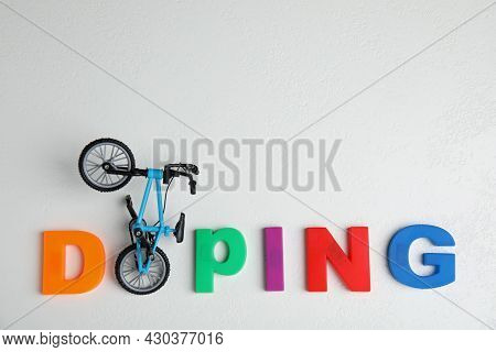 Word Doping And Bicycle Model On White Table, Flat Lay. Space For Text
