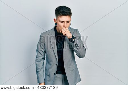 Young caucasian boy with ears dilation wearing business jacket feeling unwell and coughing as symptom for cold or bronchitis. health care concept.