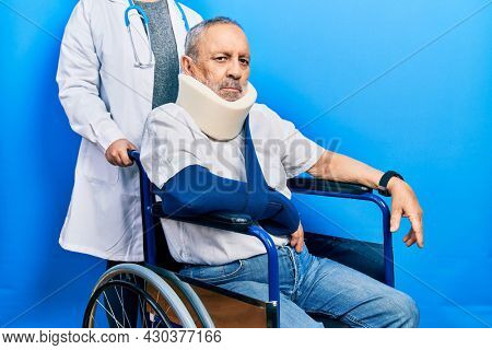 Handsome senior man with beard sitting on wheelchair with neck collar relaxed with serious expression on face. simple and natural looking at the camera.