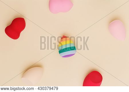 Pattern From Color Cosmetic Beauty Blender Sponges On Beige Background. Top View Multicolored Soft P