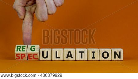 Speculation Or Regulation Symbol. Businessman Turns Wooden Cubes, Changes The Word Speculation To Re