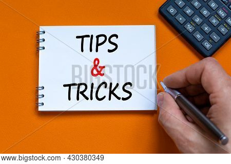 Tips And Tricks Symbol. Businessman Writing Words 'tips And Tricks' On White Note. Black Calculator.