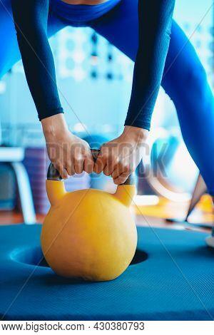 Girl In Sportswear Lifts A Heavy Yellow Kettlebell