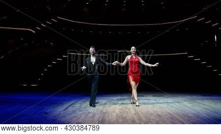 A Girl In A Red Ball Gown And A Guy In A Black Bodysuit. Dance Moves Against A Bright Background Ind
