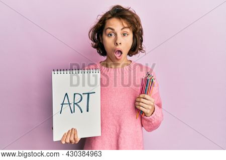 Young brunette woman holding art notebook and colored pencils afraid and shocked with surprise and amazed expression, fear and excited face.
