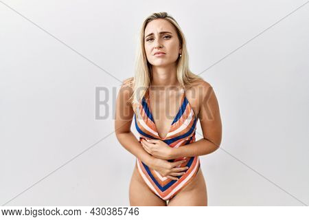 Young blonde woman wearing swimsuit over isolated background with hand on stomach because indigestion, painful illness feeling unwell. ache concept.