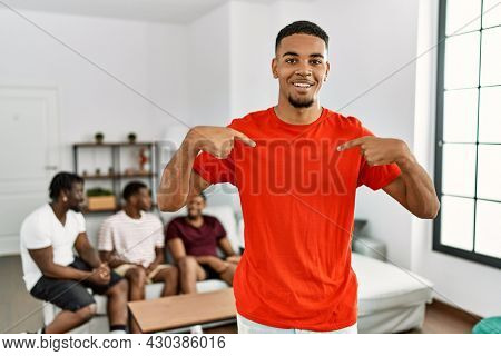 Young african man at home with friends sitting on the sofa at home looking confident with smile on face, pointing oneself with fingers proud and happy.