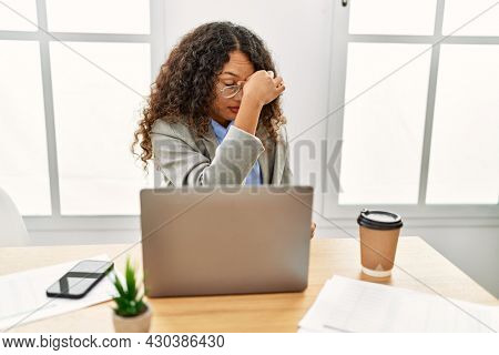 Beautiful hispanic business woman sitting on desk at office working with laptop tired rubbing nose and eyes feeling fatigue and headache. stress and frustration concept.