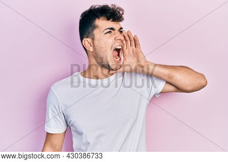 Young hispanic man wearing casual white t shirt shouting and screaming loud to side with hand on mouth. communication concept.