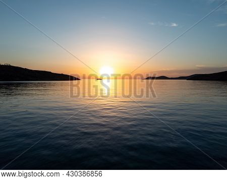 Sunset over kythnos island Merihas port Cyclades destination Greece. Last sunbeams of gold sun colors the blue sky yellow and orange and reflect on calm sparkle sea. Silhouette of landscape background