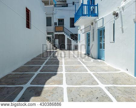 Traditional Greek architecture of whitewashed stonewall buildings closed shops empty cobblestone street. Mykonos island Chora town, Cyclades Greece. Summer vacation Greek resort destination sunny day.