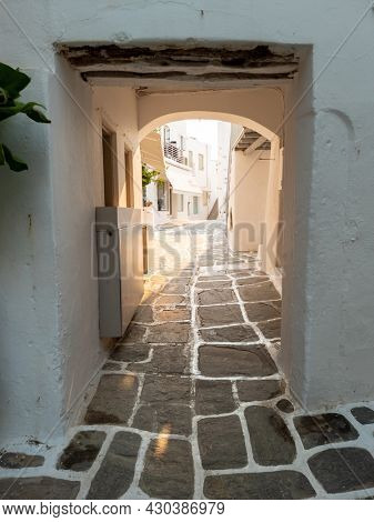 Paros island, Naousa village, Cyclades destination Greece. Greek architecture, stoa with shelter and arch covers empty narrow cobblestone alley, whitewashed stonewalls traditional buildings. Vertical