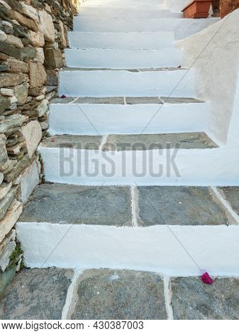 Grey empty narrow stonestairs on exterior, between stonewall and house white wall, Sifnos island Kastro village Cyclades Greece. Success climb, direction top, stairway bellow to upper way. Vertical
