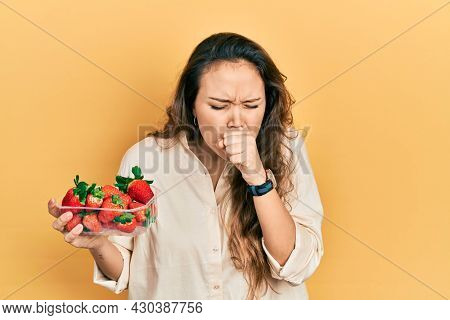 Young hispanic girl holding strawberries feeling unwell and coughing as symptom for cold or bronchitis. health care concept.