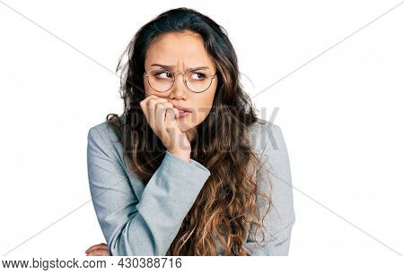 Young hispanic girl wearing business clothes and glasses looking stressed and nervous with hands on mouth biting nails. anxiety problem.