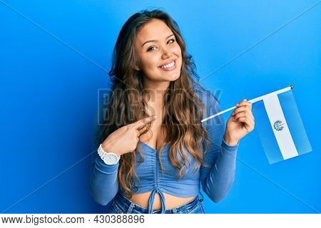 Young hispanic girl holding el salvador flag smiling happy pointing with hand and finger