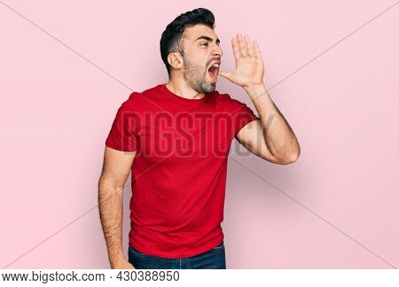 Hispanic man with beard wearing casual red t shirt shouting and screaming loud to side with hand on mouth. communication concept.