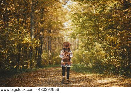 Stylish Woman Hipster With Backpack In Hat Walking In Sunny Autumn Woods. Young Female Traveler Hiki