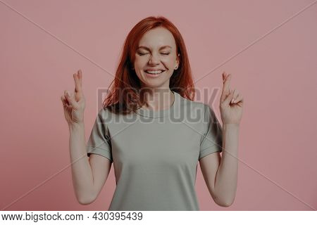 Studio Shot Of Hopeful Red-haired Female Student With Closed Eyes In Casual Wear Crossing Fingers Wi