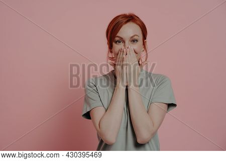 Excited Happy Red-haired Woman Covering Mouth With Hands And Looking With Surprised Facial Expressio