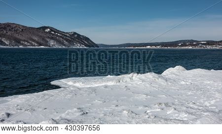 There Are Ripples On The Blue Water Of The Ice-free River. Snow On The Icy Shores. A Mountain Range