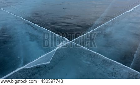 Blue Transparent Ice Of Lake Baikal. Close-up. Details. Full Screen. The Criss-crossing Cracks Go In