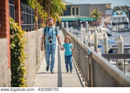 Leisure Travelers. Man And Boy Promenade Holding Hands. Leisure Activities. Father And Son Child
