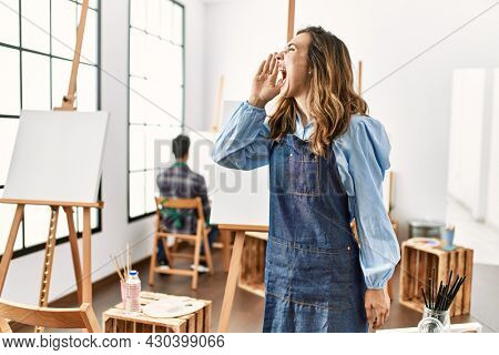 Young artist woman at art studio shouting and screaming loud to side with hand on mouth. communication concept.