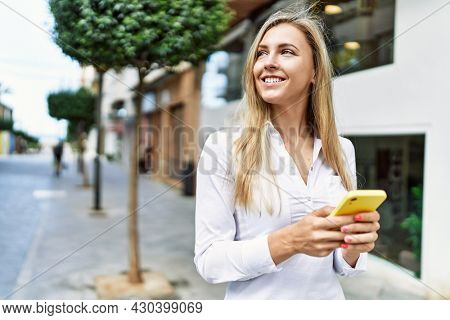 Beautiful blonde woman smiling happy outdoors on a sunny day using smartphone