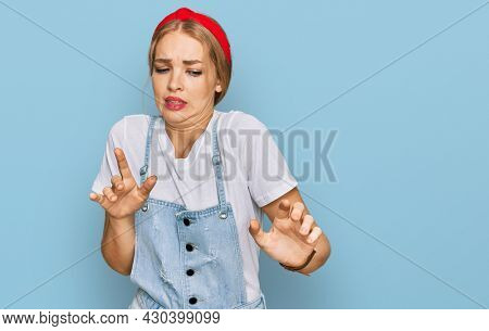 Young caucasian girl wearing casual clothes disgusted expression, displeased and fearful doing disgust face because aversion reaction.