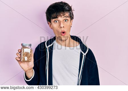 Handsome hipster young man holding lentils bowl scared and amazed with open mouth for surprise, disbelief face