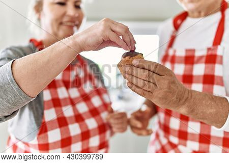 Senior caucasian couple smiling happy decorating muffin at the kitchen.
