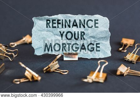 A Scrap Of Blue Paper With Clips On A Gray Background With The Text - Refinance Your Mortgage.