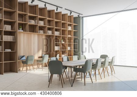 Corner View On The Large Wooden Bookcase With Niche Desk And Conference Table In The Beige And Subdu