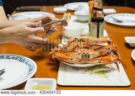 Woman Eating Crab Claw Using Special Pliers Tool