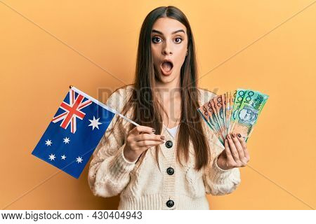 Beautiful brunette young woman holding australian flag and dollars afraid and shocked with surprise and amazed expression, fear and excited face.