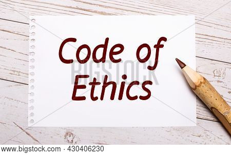On A Light Wooden Background, A Colored Pencil And A White Sheet Of Paper With The Text Code Of Ethi