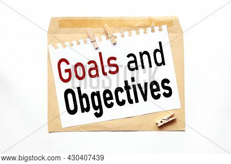 Goals And Objectives, Text On Paper On Craft Envelope On White Background