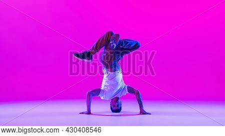 One Young Stylish Man, Break Dancing Dancer Training In Modern Clothes Isolated Over Bright Magenta